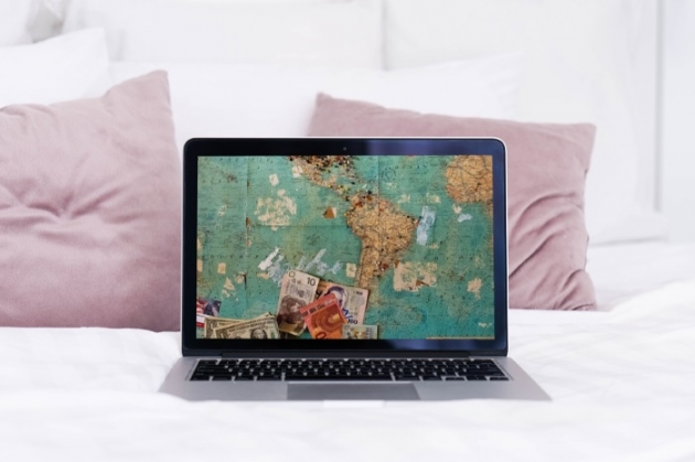 laptop on bed as an illustration how to make money as a travel blogger